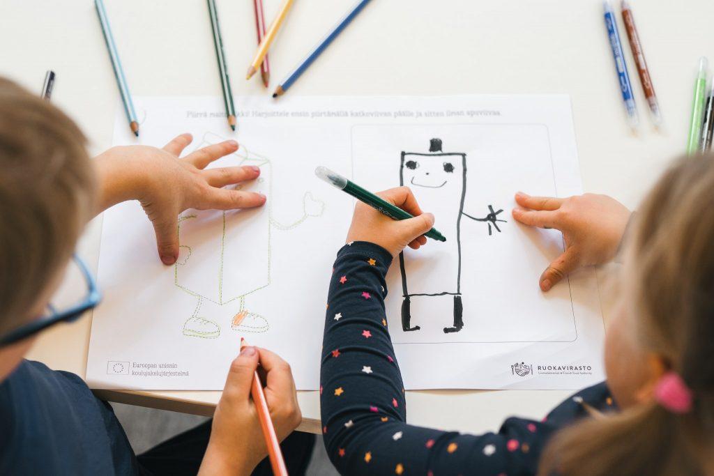 Lapset piirtävät päiväkodissa ruoka-aiheisia kuvia