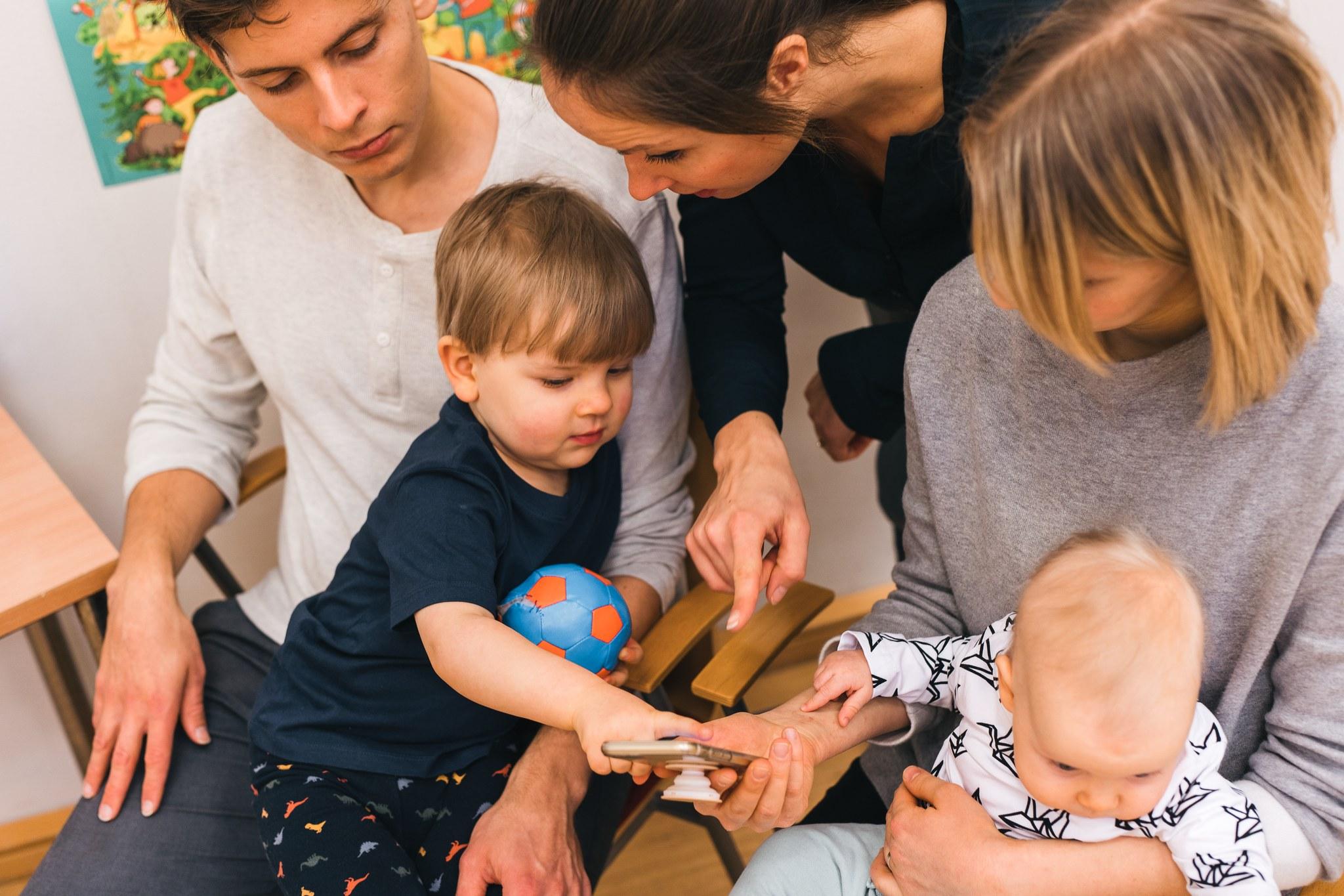 Terveydenhoitaja ja perhe katsovat digikorttia