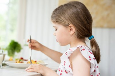 tyttö miettii ruokapöydässä