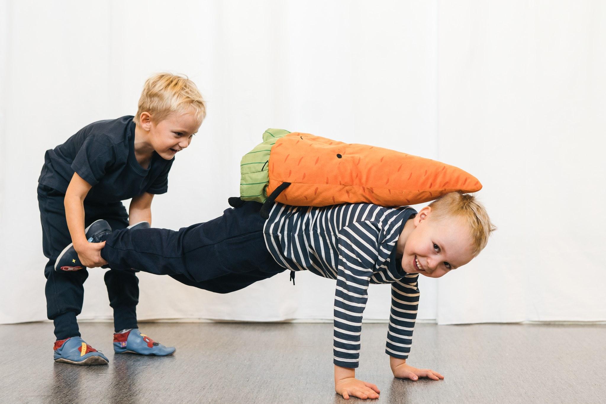 Lapset leikkivät kottikärryä